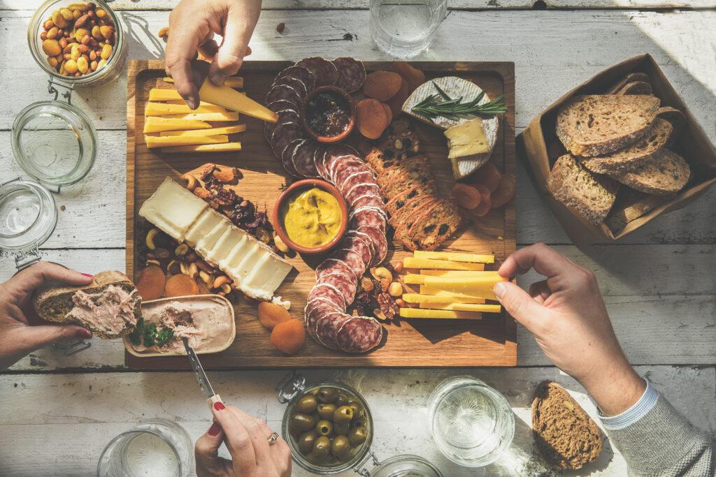 Borrelplank waar diverse mensen kaas vanaf pakken, paté op brood smeren
